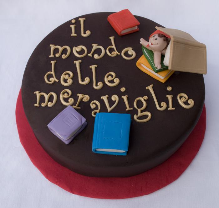 """Torta con scritta """"il mondo delle meraviglie"""" e libri colorati sparsi (con bimbo buffo che sbuca da sotto un libro)"""