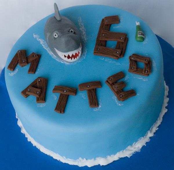 """immagine di torta con squalo e nome """"matteo"""" scritto come relitti di legno sul mare..."""