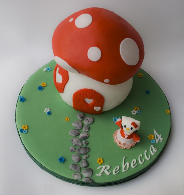 immagine di torta fatta a forma di fungo (casetta di Hello Kitty) con Hello Kitty davanti