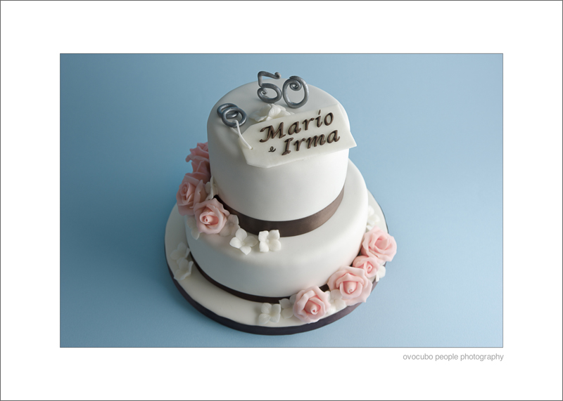 Immagine di torta a due piani con rose rosa e fiori bianchi